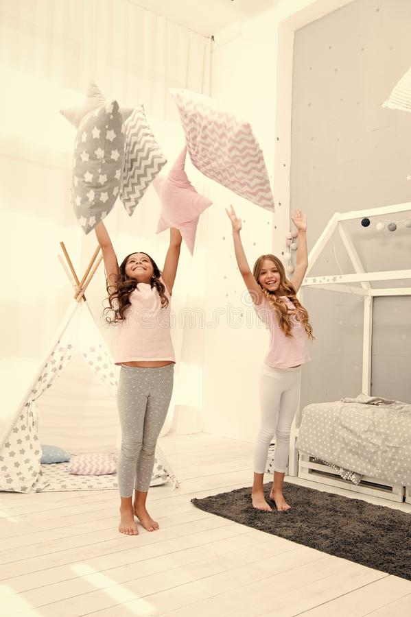Doing whatever they want. Sleepover party ideas. Sisters play pillows bedroom party. Pillow fight pajama party. Girls. Happy best friends siblings in cute royalty free stock photos