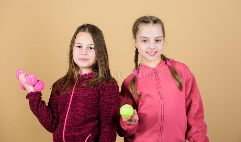Doing whatever they want. Sport success. gym workout of teen girls. Tennis racket and ball for activity. Little girl. Fitness barbell. Happy children with stock photo