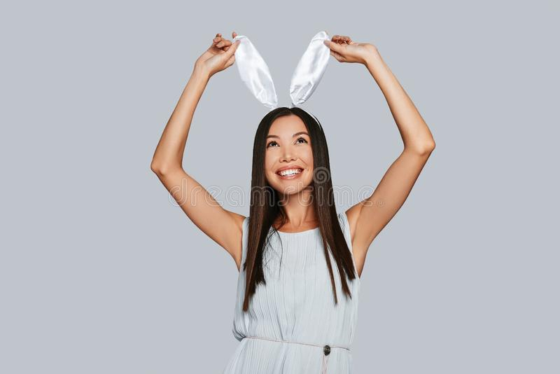 Doing whatever she wants. Beautiful young Asian woman touching her bunny ears and smiling while standing against grey background stock photos