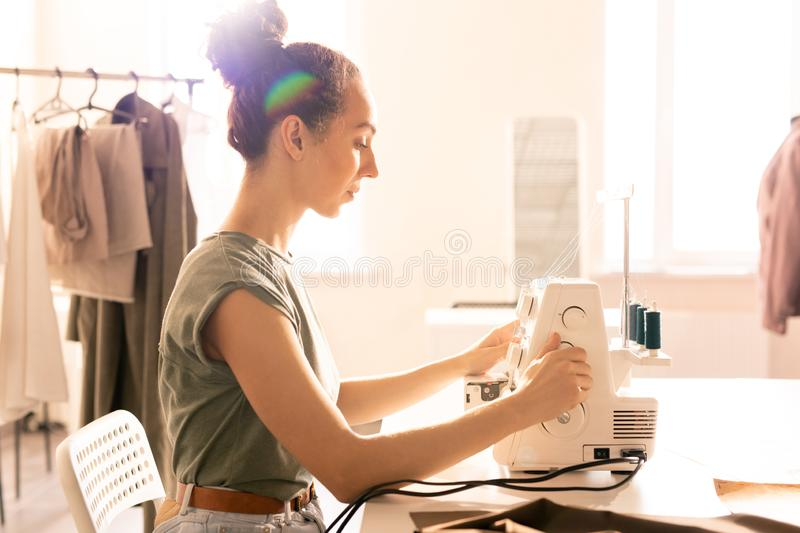 Doing work. Pretty young seamstress sitting by sewing machine on table while doing her work in studio or tailoring shop stock photography