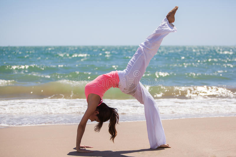 Doing yoga on a sunny day. Cute young woman practicing some yoga at the beach on a sunny day stock images