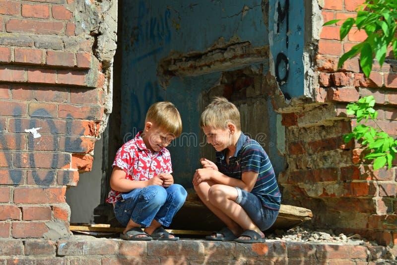 Dois órfão foram deixados desabrigados e sentando-se perto das ruínas da construção em consequência de um conflito militar, de um imagem de stock
