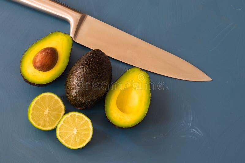 Dois abacates e e um cal no bakcground azul imagem de stock