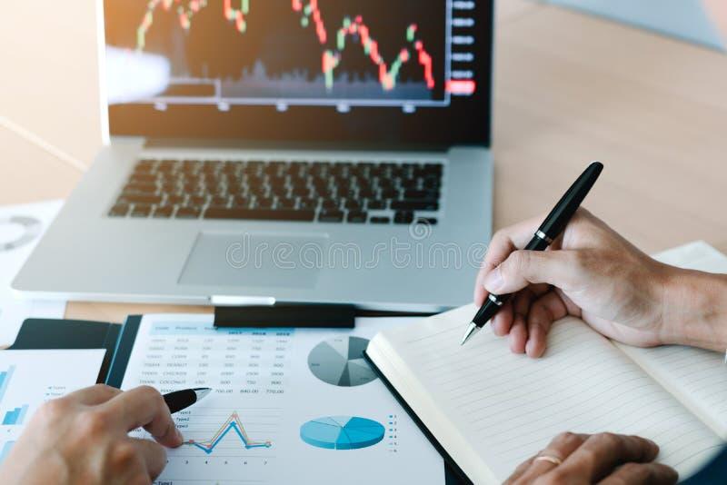Dois acionistas trabalham junto e notam a cotação das ações para comparar com outros estoques imagem de stock royalty free