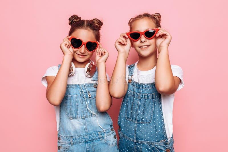 Dois adolescentes à moda no levantamento dos óculos de sol fotos de stock royalty free