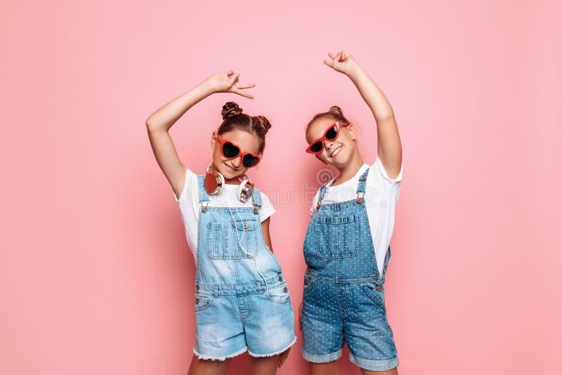 Dois adolescentes à moda nos óculos de sol que levantam em um fundo cor-de-rosa fotografia de stock