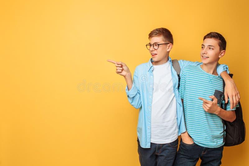 Dois adolescentes amigáveis, apontam o dedo no espaço vazio, em um fundo amarelo fotos de stock royalty free