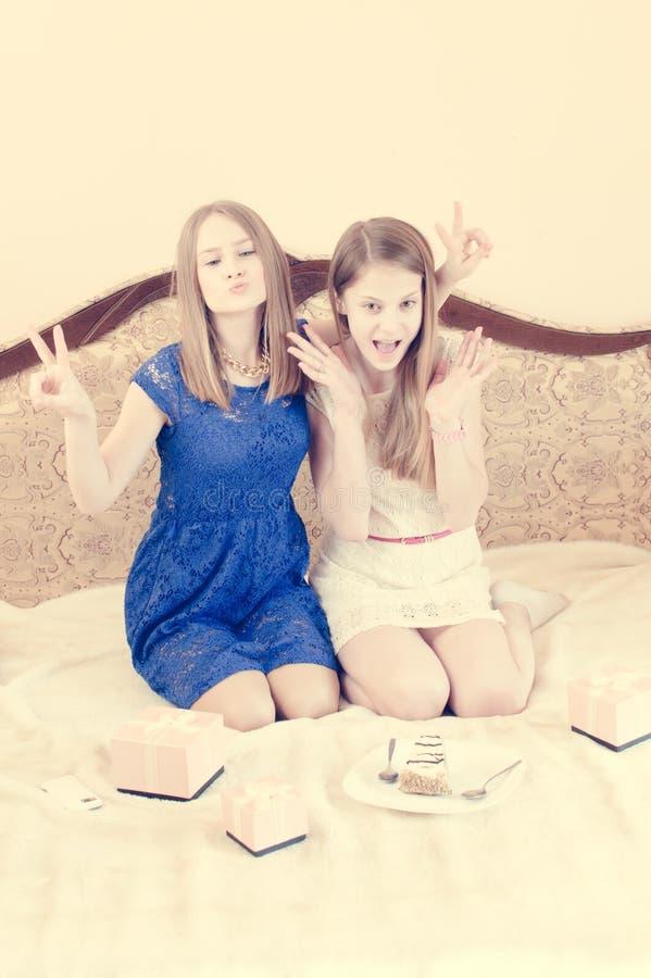 Dois adolescentes amigáveis que relaxam no sofá retro fotos de stock