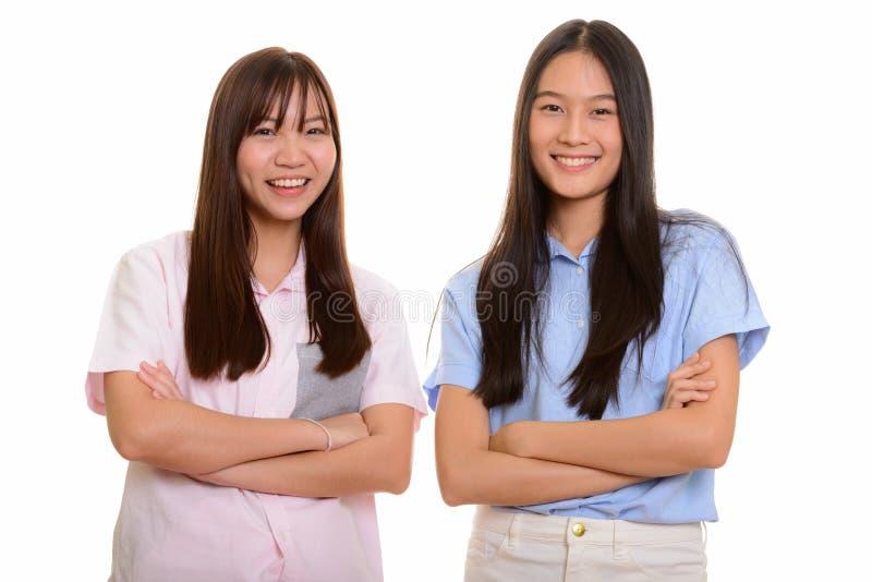 Dois adolescentes asiáticos felizes novos que sorriem com os braços cruzados fotografia de stock