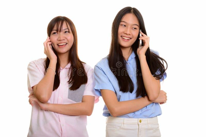 Dois adolescentes asiáticos felizes novos que sorriem e que falam em mobil imagens de stock royalty free