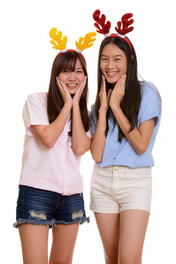 Dois adolescentes asiáticos felizes novos que sorriem e que levantam prontos para imagem de stock