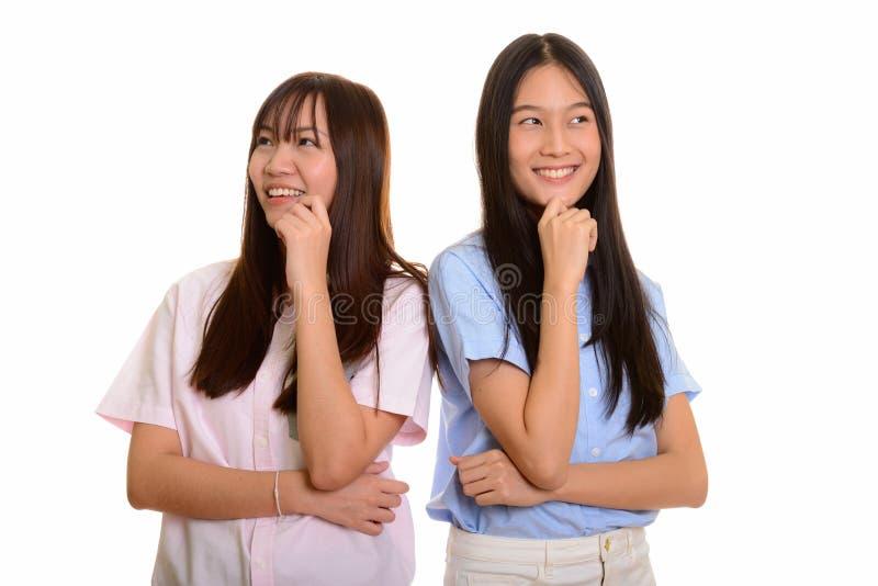 Dois adolescentes asiáticos felizes novos que sorriem e que pensam o togethe fotos de stock