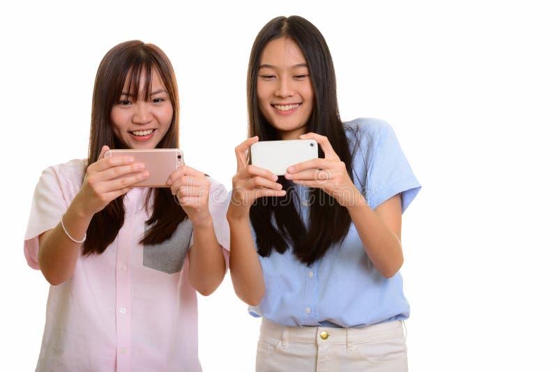 Dois adolescentes asiáticos felizes novos que sorriem e que tomam a imagem w imagens de stock royalty free