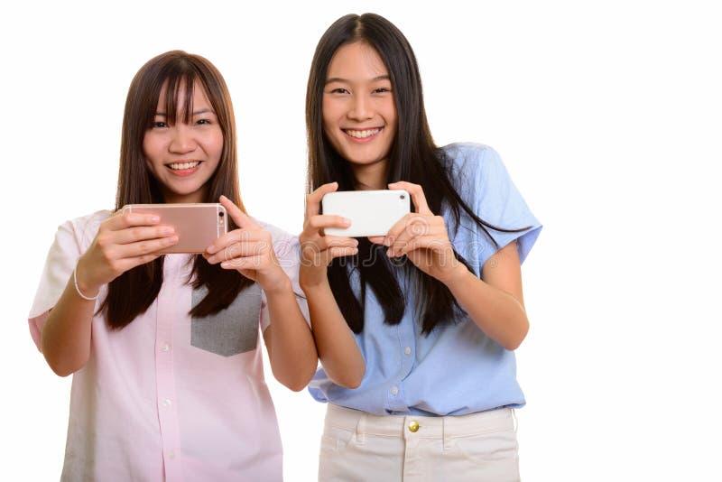 Dois adolescentes asiáticos felizes novos que sorriem e que tomam a imagem w imagem de stock royalty free