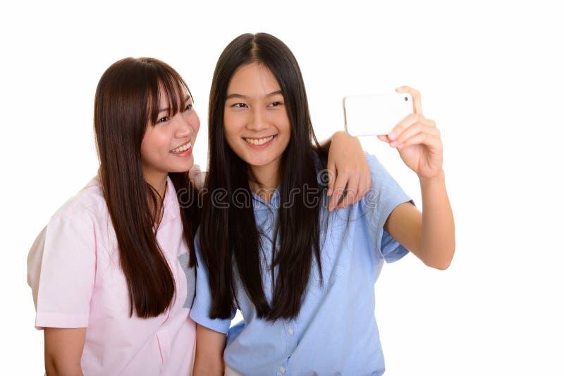 Dois adolescentes asiáticos felizes novos que sorriem e que tomam wi do selfie imagem de stock