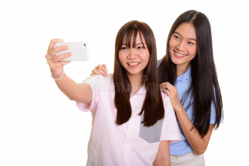 Dois adolescentes asiáticos felizes novos que sorriem e que tomam wi do selfie imagens de stock