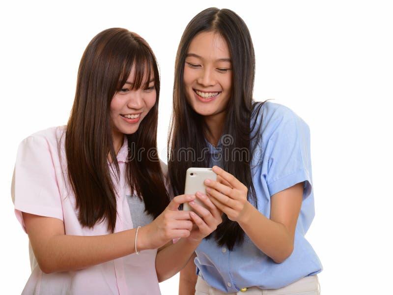 Dois adolescentes asiáticos felizes novos que sorriem e que usam o pho móvel fotografia de stock royalty free
