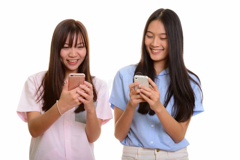 Dois adolescentes asiáticos felizes novos que sorriem e que usam o pho móvel foto de stock