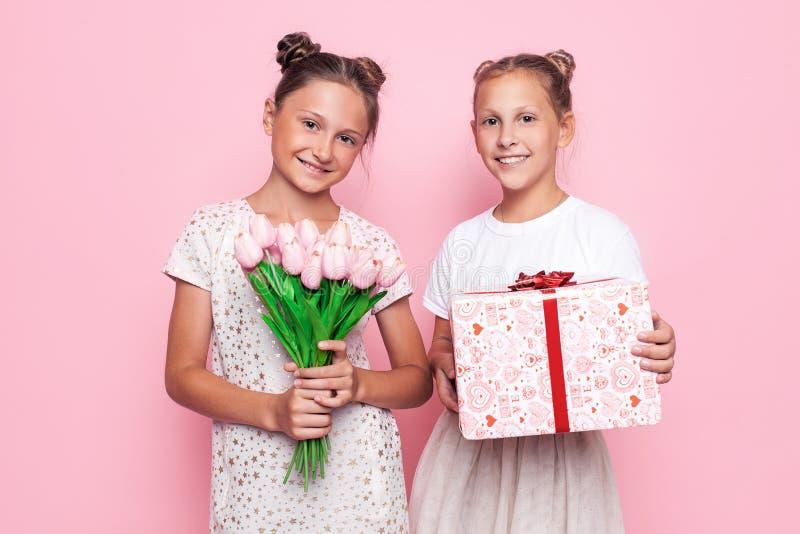 Dois adolescentes bonitos em vestidos delicados com um presente e um ramalhete das flores em suas mãos dão presentes imagem de stock