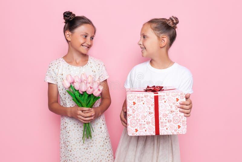 Dois adolescentes bonitos em vestidos delicados com um presente e um ramalhete das flores em suas mãos dão presentes fotografia de stock