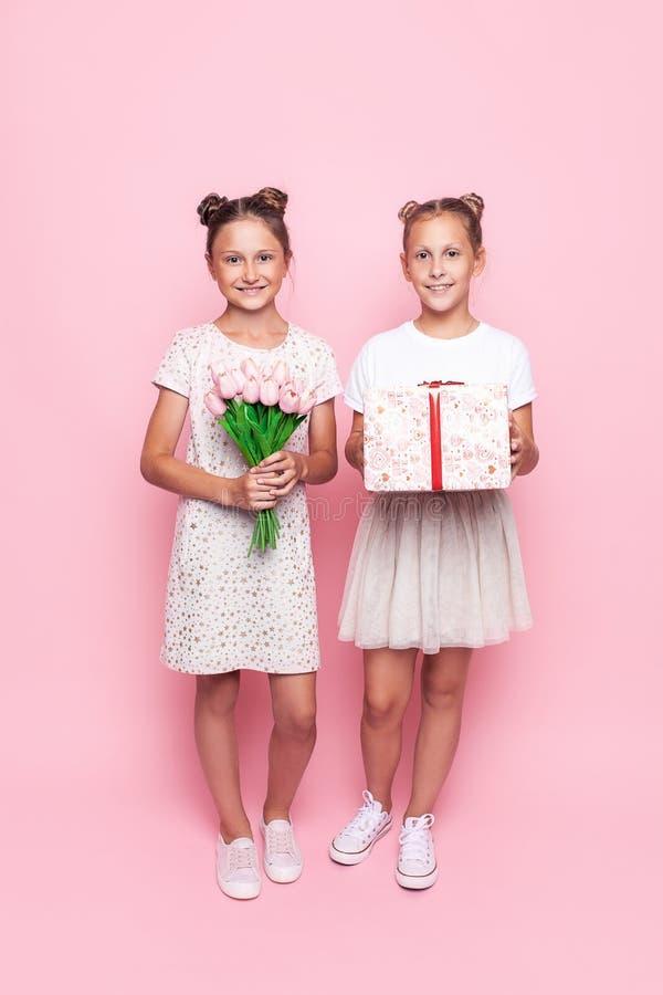 Dois adolescentes bonitos em vestidos delicados com um presente e um ramalhete das flores em suas mãos dão presentes imagens de stock