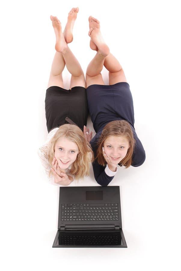 Dois adolescentes bonitos que encontram-se no assoalho e no Internet surfando no portátil imagens de stock royalty free
