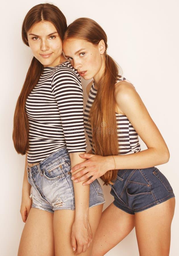 Dois adolescentes bonitos que têm o divertimento junto no branco imagem de stock