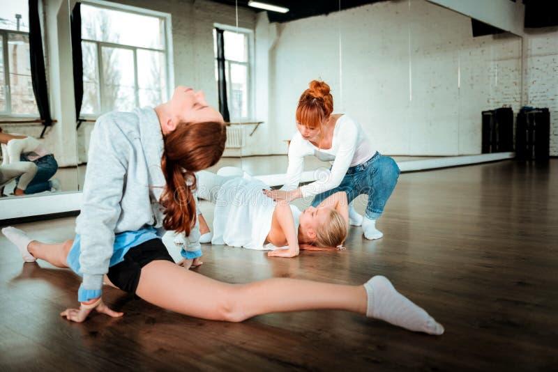 Dois adolescentes da geração z que faz exercícios para esticar sob seu controle dos professores imagem de stock
