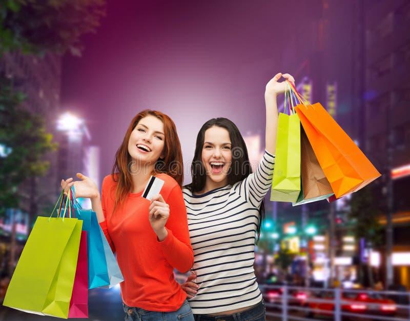 Dois adolescentes de sorriso com sacos de compras imagens de stock royalty free