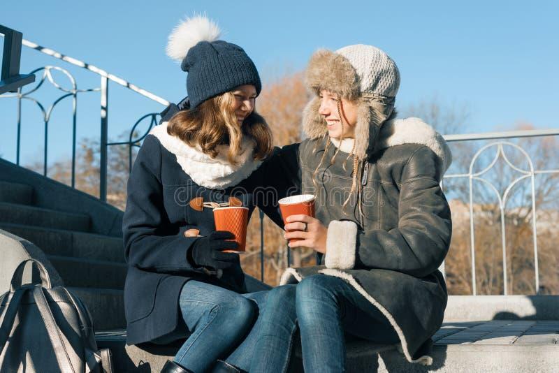 Dois adolescentes novos que têm o divertimento fora, amigas na roupa do inverno, povos positivos e conceito da amizade Beber das  fotos de stock royalty free