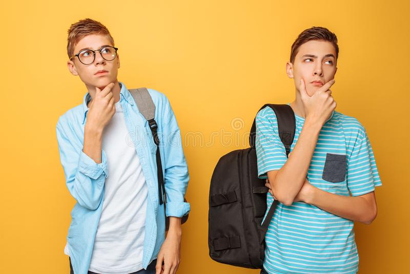 Dois adolescentes pensativos, indivíduos que estão tentando encontrar a solução direita ou fazer planos, em um fundo amarelo imagem de stock royalty free