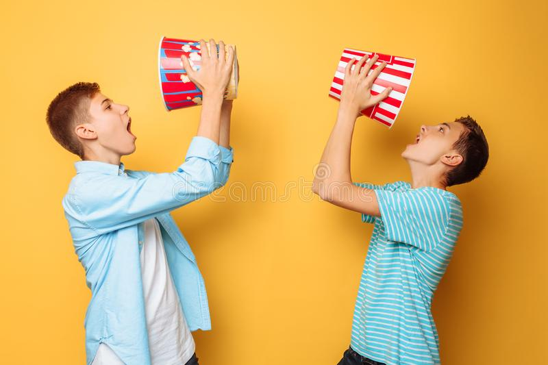 Dois adolescentes que comem a pipoca e que têm o divertimento em um fundo amarelo foto de stock