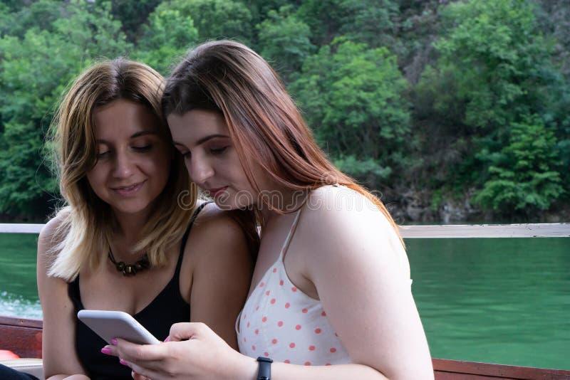 Dois adolescentes que olham um vídeo em um telefone celular, e riso, sentando-se em um barco Amigos de meninas caucasianos dedica imagem de stock royalty free