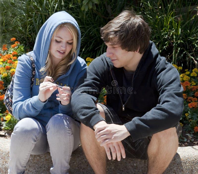 Dois adolescentes que sentam-se e que falam fotos de stock royalty free