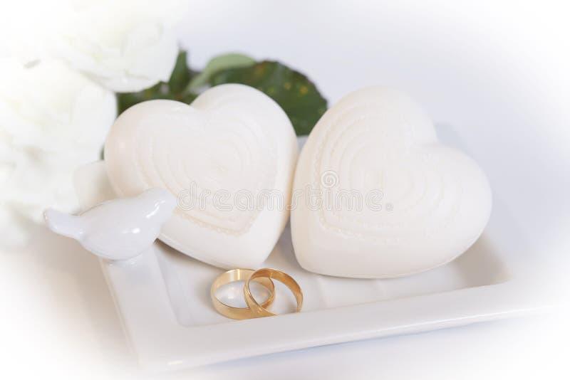 Dois alianças de casamento e corações do ouro fotos de stock royalty free