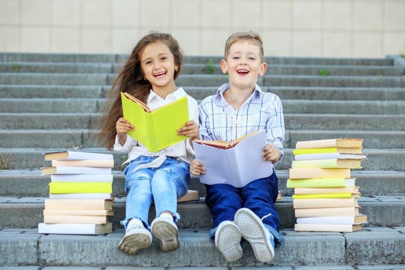 Dois alunos leram livros e riso O conceito é de volta à escola, à educação, à leitura, à amizade e à família imagens de stock