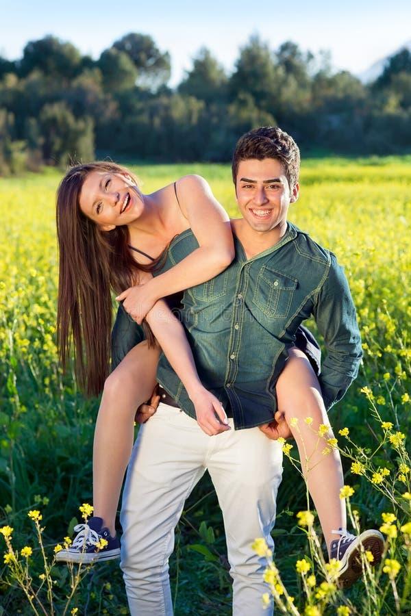 Dois amantes novos em um campo da colza amarela. foto de stock