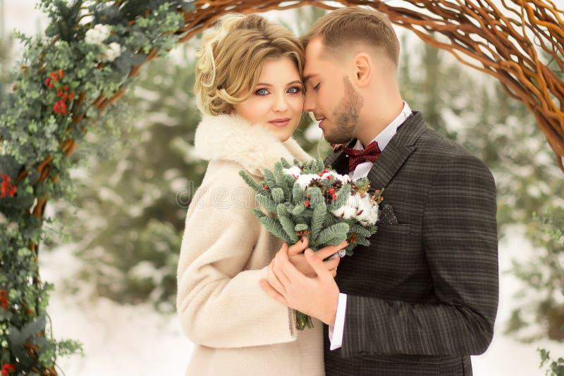 Dois amantes, um homem e uma mulher, um casamento no inverno Amor dos noivos contra o contexto da decoração e das árvores, neve G imagens de stock