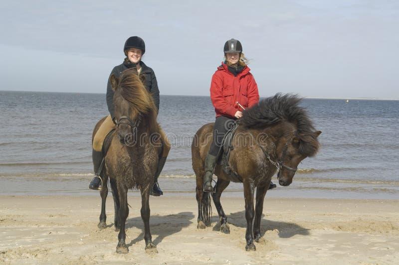 Dois amazones no horseback na praia imagens de stock