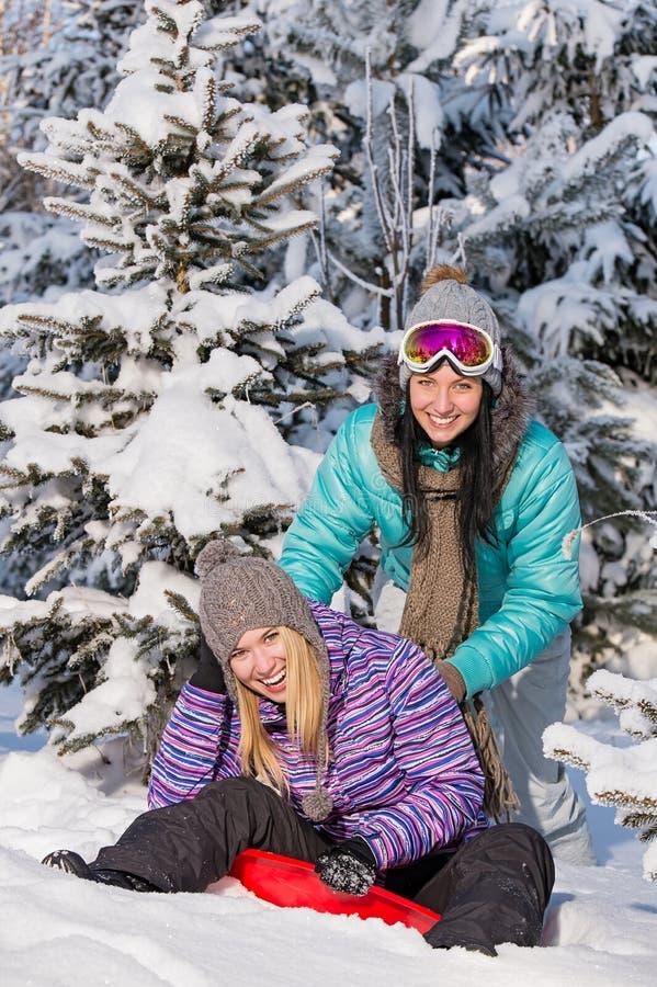 Dois amigos adolescentes apreciam o trenó da neve do inverno imagens de stock