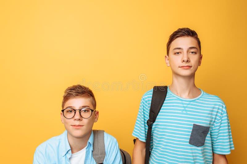 Dois amigos adolescentes, um indivíduo humilham o outro, popular humilham o impopular, em um fundo amarelo imagem de stock