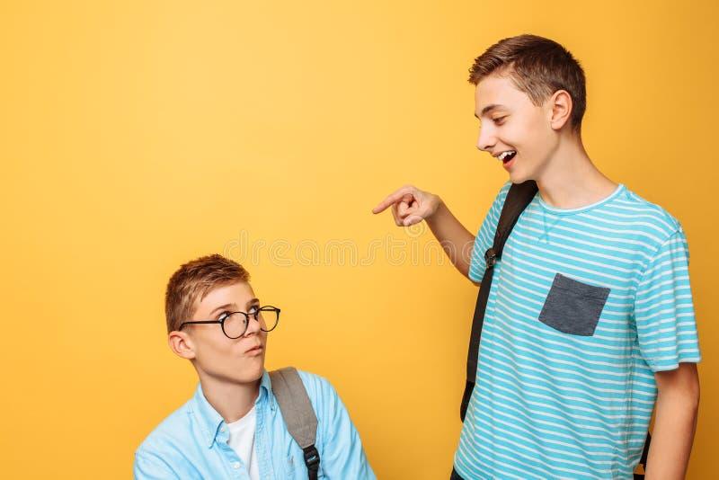 Dois amigos adolescentes, um indivíduo humilham o outro, popular humilham o impopular, em um fundo amarelo fotografia de stock
