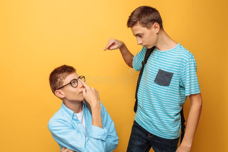 Dois amigos adolescentes, um indivíduo humilham o outro, popular humilham o impopular, em um fundo amarelo fotos de stock