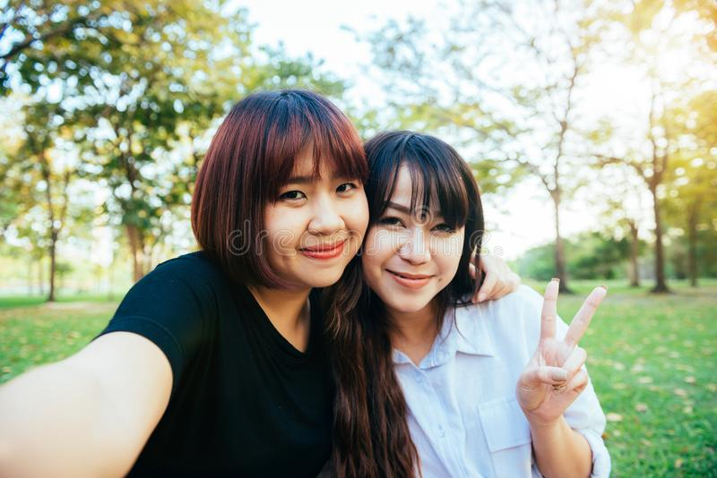 Dois amigos asiáticos novos felizes bonitos das mulheres que têm o divertimento junto no parque e que tomam um selfie fotos de stock royalty free