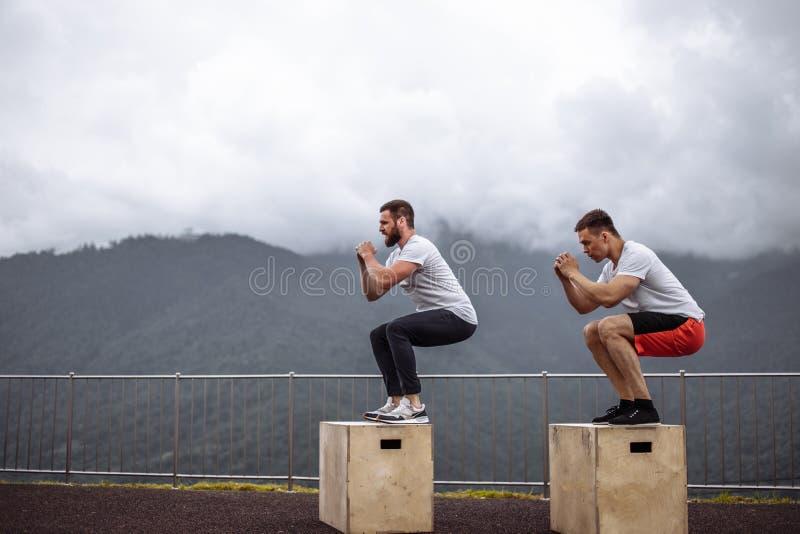 Dois amigos atléticos masculinos que fazem a caixa saltam exterior sobre a montanha imagem de stock royalty free