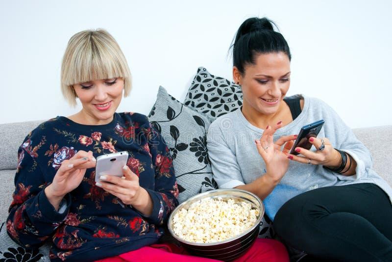 Dois amigos atrativos da mulher com telefone celular e pipoca foto de stock royalty free