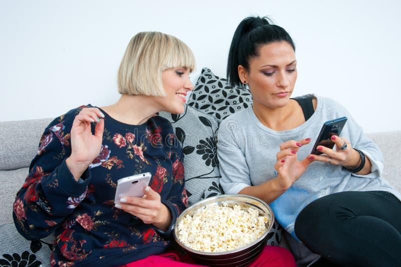 Dois amigos atrativos da mulher com telefone celular e pipoca imagem de stock