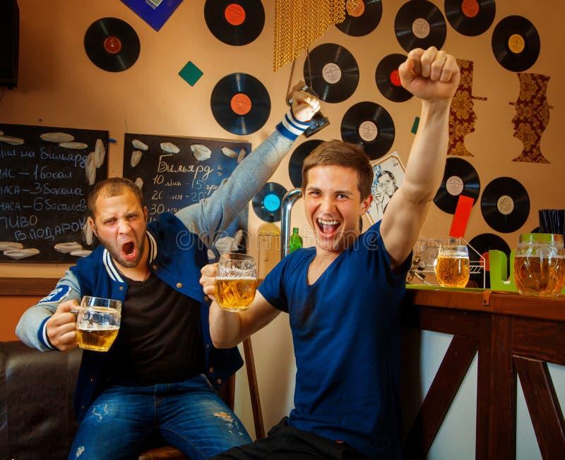 Dois amigos bebem a cerveja na barra e têm o divertimento fotografia de stock