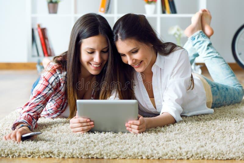 Dois amigos bonitos da jovem mulher que usam a tabuleta digital em casa imagem de stock