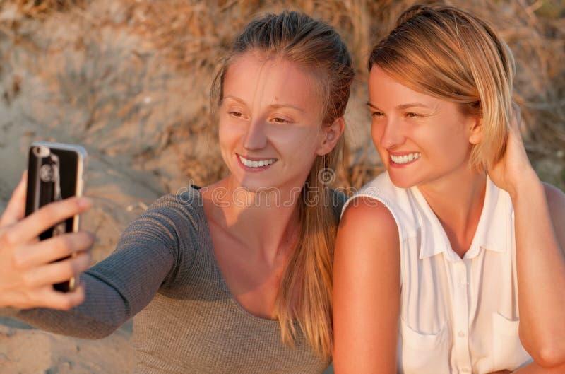 Dois amigos bonitos das mulheres que tomam fotos com um telefone esperto na praia no por do sol fotografia de stock